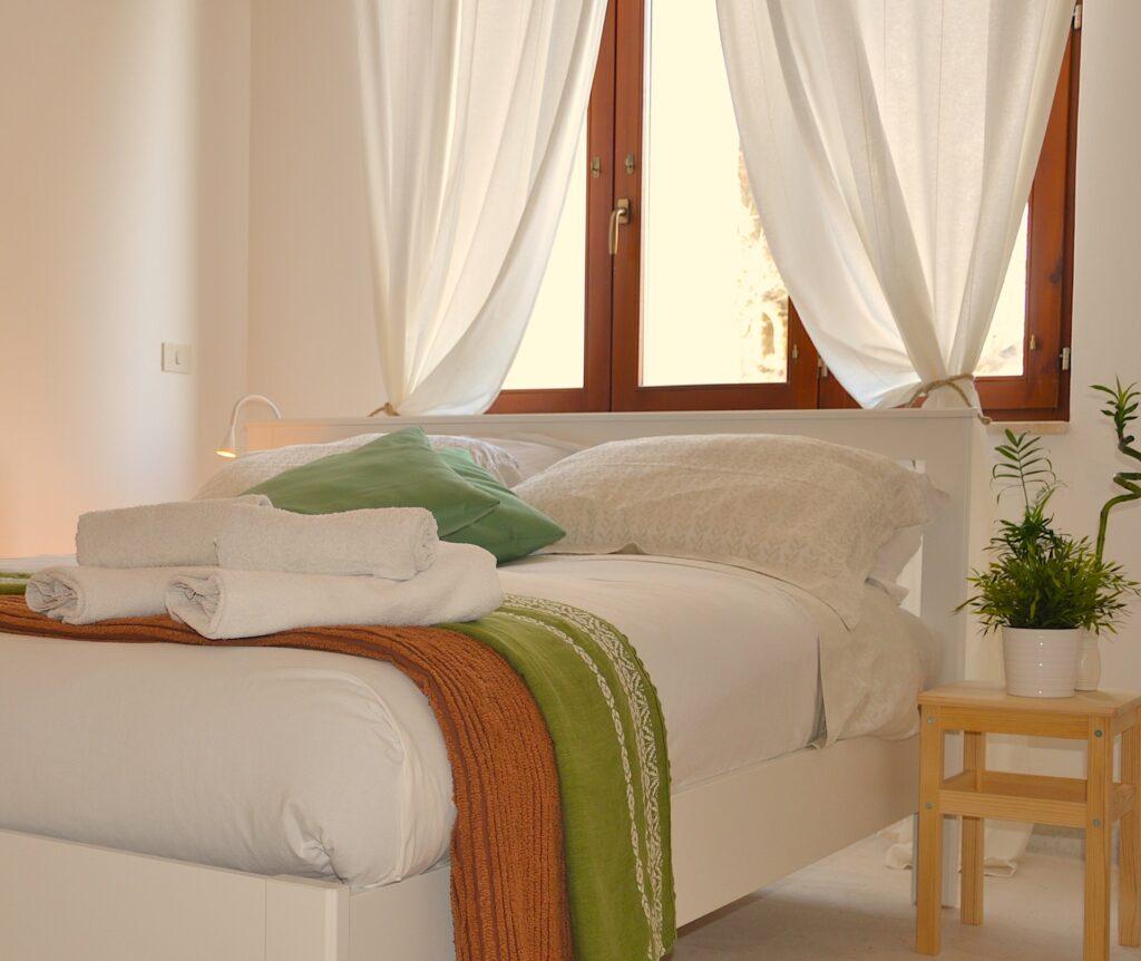 Camera di hotel con letto matrimoniale sotto amp[ia finestra