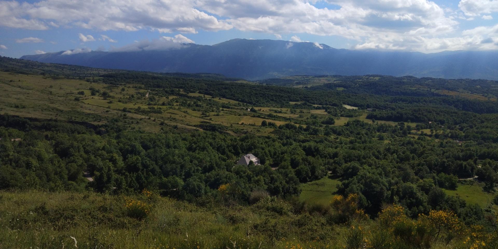 Ecolodge vista dall'alto e circondata dal bosco rigoglioso, con il massiccio montuoso Majella all'orizzonte