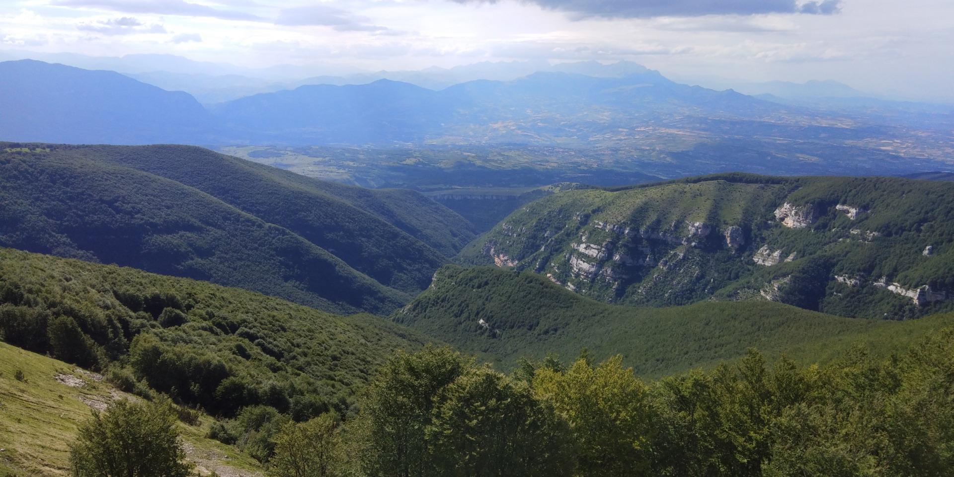 Vista panoramica sulla Majella con montagne verdi e vette coperte da nuvole all'orizzonte