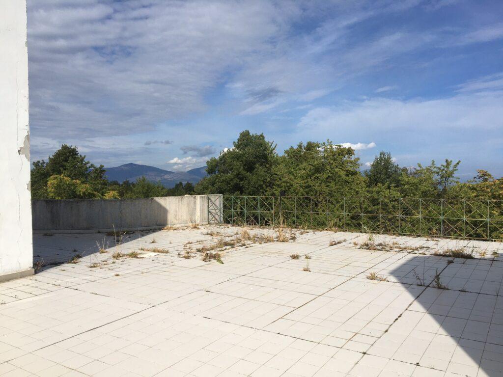 Terrazza dell'ecolodge con pavimento dissestato ed erbacce