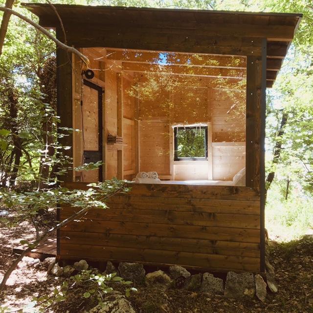 cabina glamping con parete a vetro vista dall'esterno