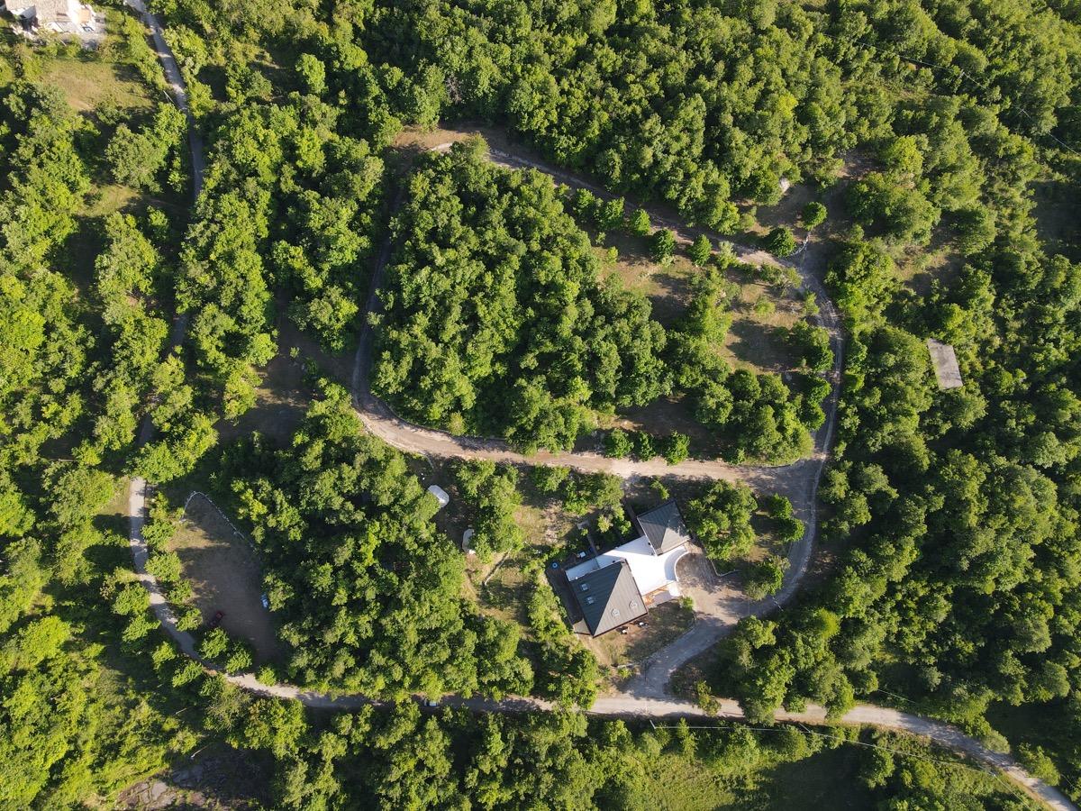 dimore montane e intera area campeggio nel bosco visti dall'alto